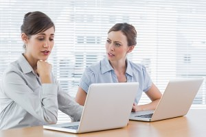 Worried businesswomen working on email etiquette at desk in office